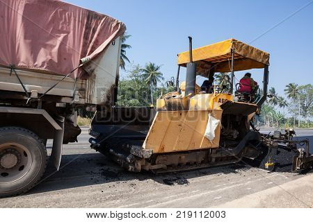 an asphalt machine and an truck with trailer for the renewal of the asphalt