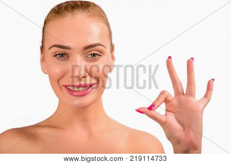 Braces. Beautiful Woman smile and showing an OK sign close up. Healthy Smile. Closeup Ceramic Braces on Teeth. Beautiful Female Smile with Braces. Orthodontic Treatment. Dental care Concept.