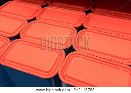 Rows of red plastic lids with blue containers for background.