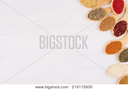 Asian spices in wooden quaint spoons on soft white board closeup.