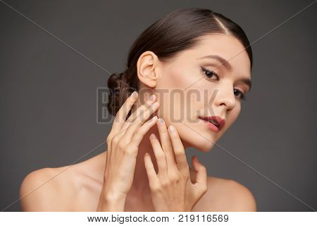 Attractive young woman touching her beautiful face
