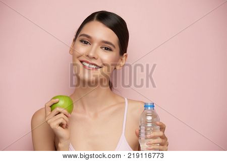 Beautiful young woman with bottle of water and green apple