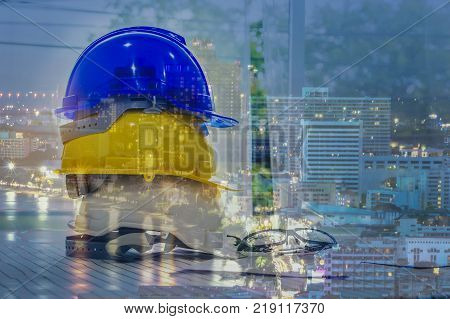 Double exposure of engineer helmet for architectural project and working with partner engineering on workplace and background night city scape.