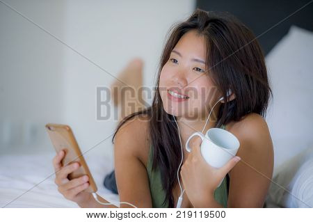 young beautiful and relaxed Asian Chinese woman with earpiece listening to music smiling happy lying on bed at home bedroom using internet on mobile phone drinking morning coffee cup