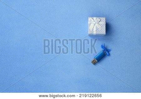 Brilliant blue usb memory card with a blue bow lies next to a small gift box in blue with a small bow on a blanket of soft and furry light blue fleece fabric. Classic female gift memory card design