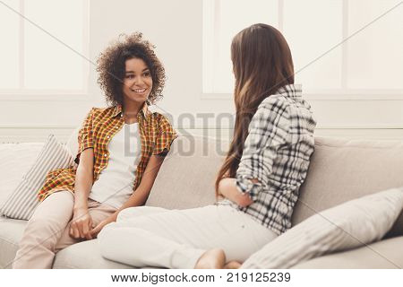 Two happy young female friends talking in living room at home, chatting about their life and relations, gossip and slumber party concept, copy space