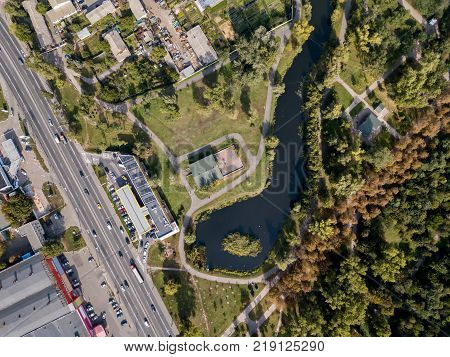 Green cityscape with a park, lake and a roadway in Kyiv. Top view panoramic photo. Horizontal.