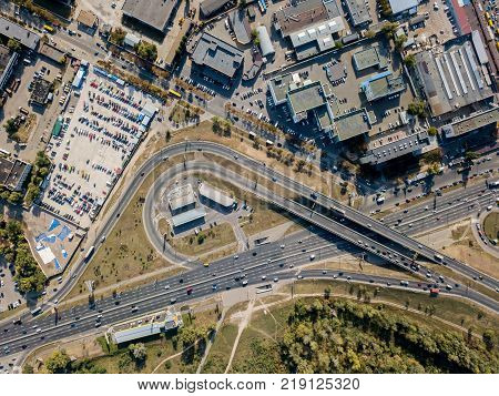 Roadway with bridge in Kyiv. There is a park, car parking and buldings around it. Top view panoramic photo. Horizontal.