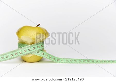 Yellow ripe bitten apple with a meter on a white background.Сopy space