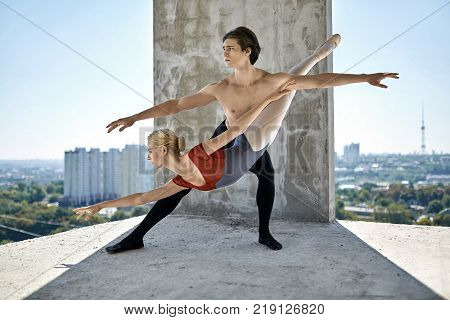 Young couple of ballet dancers posing on the concrete floor of the unfinished building on the cityscape background. Topless guy wears a black dance pants, girl wears a red-gray leotard. Horizontal.