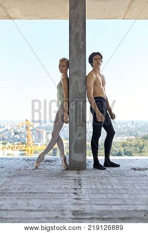 Serious couple of ballet dancers lean on the concrete wall on the floor of the unfinished building on the cityscape background. Topless guy wears a black dance pants, girl wears a green leotard.