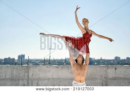 Topless dancer holds a ballerina over his head on the background of the concrete wall and cityscape. Guy wears a white dance pants. Girl wears a red skirted leotard, light leggings and pointe shoes.