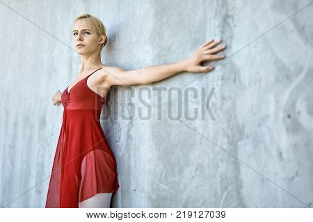 Pretty ballerina leans on the concrete wall with outstretched to the sides arms. She wears a red skirted leotard with light leggings. Girl looks forward. Sun shines onto her body. Closeup. Horizontal.