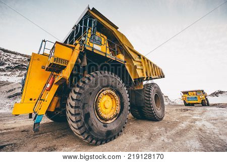 Big trucks working in an open pit. Coal mine. Mining