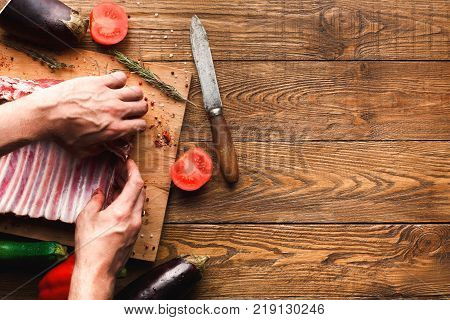 Man preparing rack of lamb on wooden board at restaurant kitchen. Chef preparing fresh meat for cooking. Modern cuisine backgroung with vegetables and meat with copy space, top view