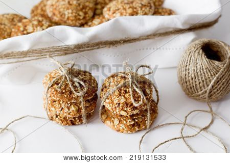 Oats cookies on a white table in rustic style. seeds, basket of fabric for baking. front horizontal view