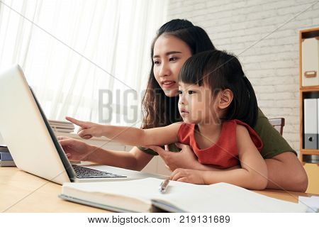 Young Asian woman teaching her daughter how to work on