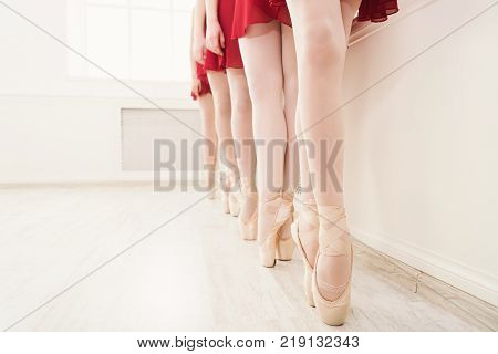 Ballet background, young ballerinas training. Female dancers legs in pointe shoes, making exercises. Classical dance school, copy space, crop