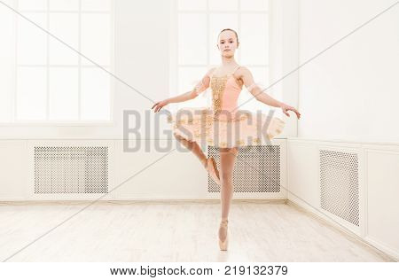 Young teenager ballerina exercising in ballet costume, standing on her toes. Ballet student practicing classical dance pas in studio before performance