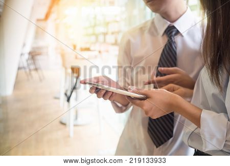 business meeting Image of two young business people using touchpad tablet.