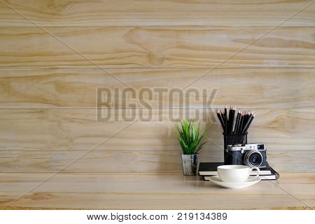 office supplies cameracoffee cup plant decoration and pencils on wood desk and wood wall with empty copy space for present something.