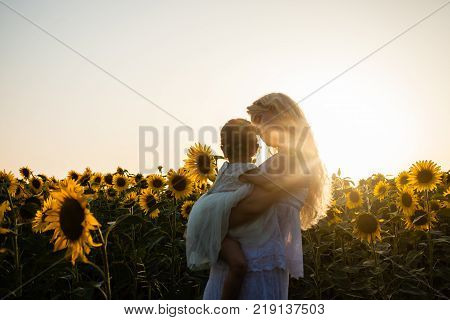Happy mother hugs her daughter in a sunflower field, white clothes