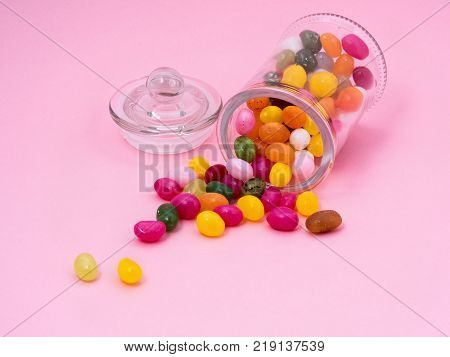 jelly sweet candy of different colors scattered on a pink background from the glass jar with a lid. Dyes and preservatives.