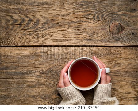 Female hands holding a mug of hot black tea. Cold winter white warm clothes. Top view. Aged rustic wooden background