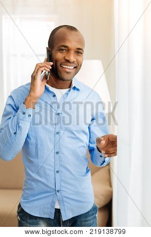 Phone talk. Good-looking alert well-built afro-american man standing near the window and grinning while talking on the phone