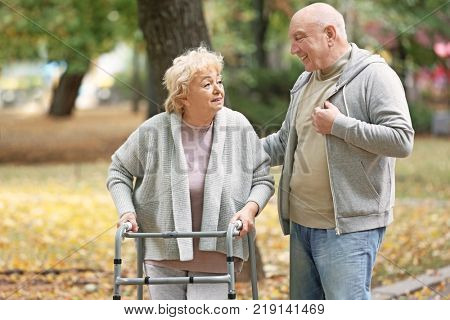 Elderly man and his wife with walking frame in autumn park