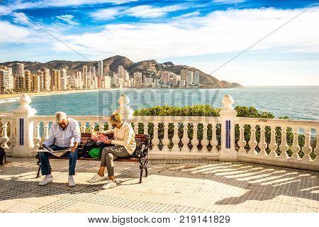 BENIDORM, SPAIN, DECEMBER 14, 2017: Eldery couple relax sitting on the bench in Mediterranean Balcony in Benidorm, Spain