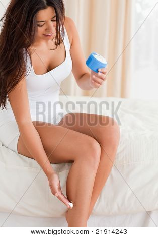 Smiling Woman Putting Creme On Her Legs