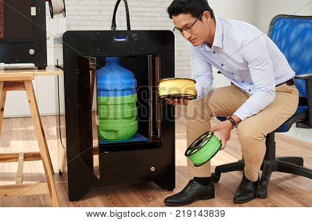 Asian young woman choosing filament to load in 3D printer