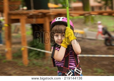 Girl in a helmet and safety equipment in adventure ropes park get down in the end of way