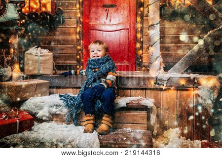 Cute little boy in winter clothes sits on the porch of the magic house of Santa Claus. Miracle time. Merry Christmas and Happy New Year.