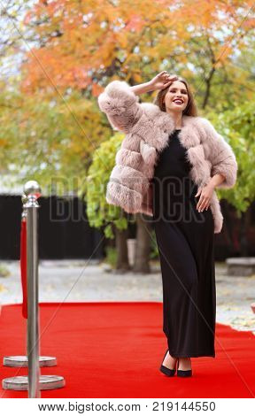 Beautiful young woman in black dress and fur coat on red carpet, outdoors