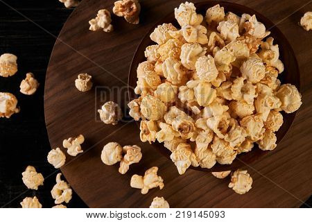 Popcorn in wooden bowl. Hot pop corn with salted caramel in bowl on wooden table, close-up. Top view. Movie time concept