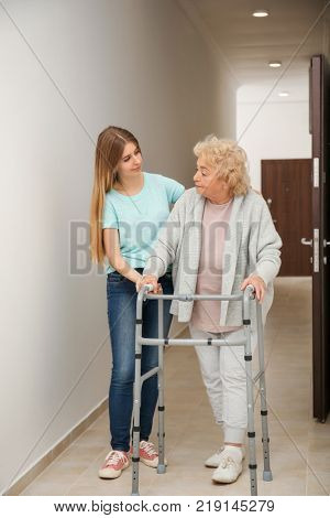 Young woman and her elderly grandmother with walking frame in corridor