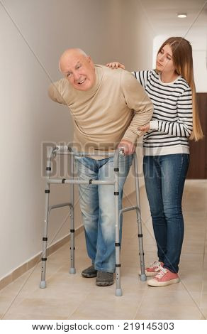 Young woman and her elderly grandfather with walking frame in corridor