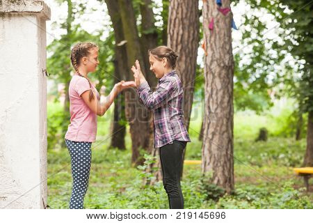 Two girls are playing hands clapping game outdoors, teenagers friendship
