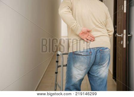 Elderly man with walking frame in corridor