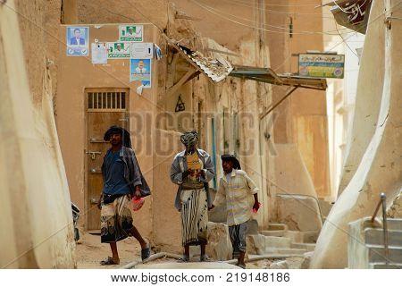 SHIBAM, YEMEN - SEPTEMBER 12, 2006: Unidentified men walk by the street in Shibam, Yemen.