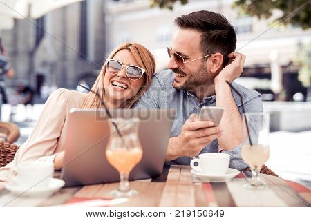 Happy couple sitting in street cafe together and using laptop and phone.