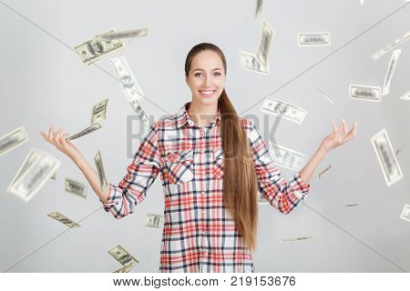 happy woman in plaid shirt is standing under money rain. money falls on girl