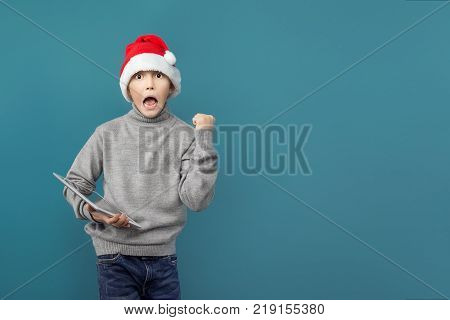 Cute boy in Christmas hat standing with tablet and celebrating with fist up.