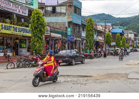 POKHARA NEPAL - October 2 2013: Girl on a scooter on the streets of Pokhara. Pokhara is the starting point for most of the treks in the Annapurna area.