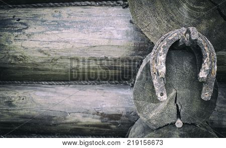 Horseshoes hang on an iron nail driven into the wall of a wooden house. People's sign for luck