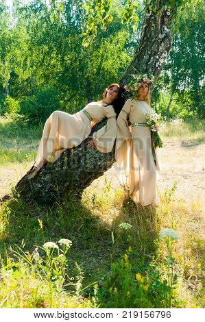 Attractive women in traditional russian clothes relaxes over nature background. Ivan Kupala Holiday Celebration