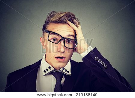 Desperate shocked defeated young business man with glasses