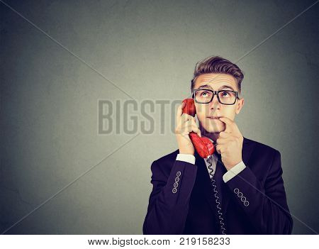 Misunderstanding and distant call. Upset worried confused man talking on a phone has many questions isolated on gray background.